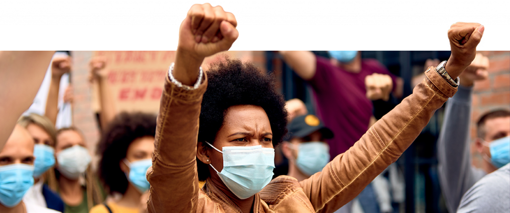 Black woman with medical mask raises both fists in triumph